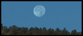 Banner photo of a full moon setting behind the hill.